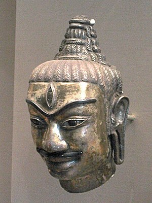 Champa - This Cham head of Shiva was made of electrum around 800. It decorated a kosa, or metal sleeve fitted to a liṅgam. One can recognise Shiva by the tall chignon hairstyle and by the third eye in the middle of his forehead.