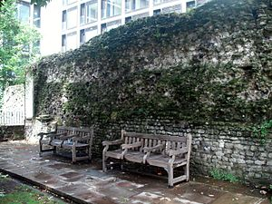 Photograph of park benchs placed against a section of the London Wall in a public city garden.