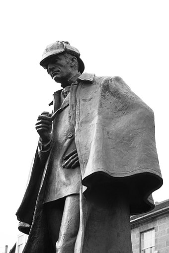 Statue of Holmes in an Inverness cape and a deerstalker cap on Picardy Place in Edinburgh (Conan Doyle's birthplace) Statue of Sherlock Holmes in Edinburgh.jpg