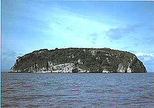 A rocky island with steep sides rises sharply out of the water.