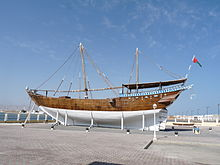 An Arabian dhow, a ship constructed with a covered area at the rear and no real superstructure. They are used as cargo vessels and have one or two masts with triangular sails.
