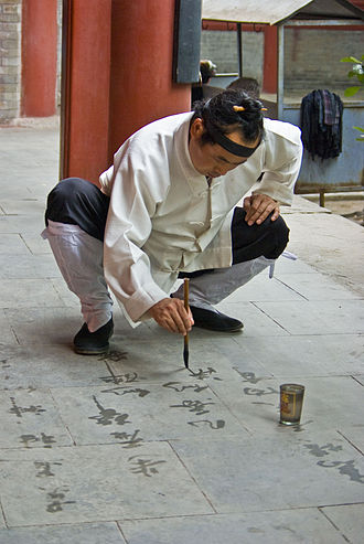 Tao - A Taoist monk practicing Chinese calligraphy with water on stone. Water calligraphy, like sand mandalas, evokes the ephemeral nature of physical reality.