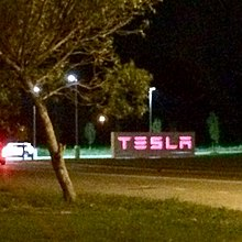 "Large white sign with red letters spelling ""TESLA"""