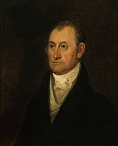 A man with receding, dark hair wearing a high-collared white shirt, a vest, and a black jacket