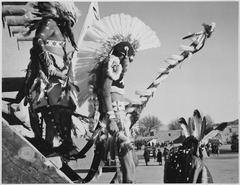 "Three Indians in headdress in foreground watching tourists, ""Dance, San Ildefonso Pueblo, New Mexico, 1942."", 1942 - NARA - 519979.tif"