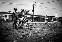 To barn som reiser gjennom nabolaget sitt ved hjelp av en sykkel som hver deltar i alt