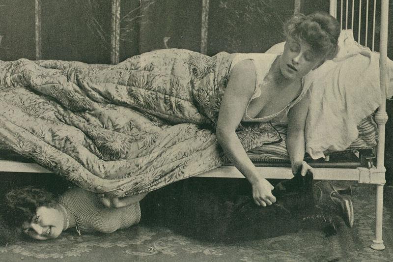 Amantă ascunsă sub patul femeii în pijama
