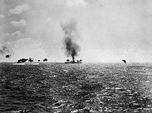 Nuage de fumée s'élevant d'un navire vu de profil, et diverses explosions ou volutes de fumée à la surface de la mer