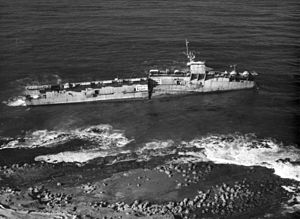 USS Makassar Strait - ex-Makassar Strait aground as a target ship in the early 1960s. Note Warning painted on Hull.