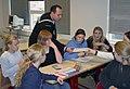 US Navy 031006-N-2280S-001 Electronics Tecnichian 1st Class Chris Wright checks the work of a group of eighth-grade math students.jpg
