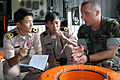 US Navy 060620-N-9330Y-005 Royal Thai Navy Lt. Nara Khunthothom, left and Lt. Eakkalak Panson, center, listen attentively as Mineman 2nd Class Matthew Greene of Mobile Mine Assembly Unit Ten (MOMAU-10) concludes training on the.jpg