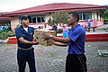 US Navy 080710-N-0096V-029 Ens. Justan Caesar, assigned to the amphibious dock landing ship USS Tortuga (LSD 46), hands supplies to a Royal Malaysian Sailor.jpg