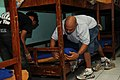 US Navy 091223-N-1008D-013 U.S. Army Master Sgt. Robert Garo, assigned to Joint Special Operations Task Force-Philippines (JSOTF-P), and a staff member of the Social Development Center make up beds with linen donated from JSOTF.jpg