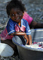 US Navy 100118-N-5244H-013 A young Haitian girl takes a pause from washing laundry watch the U.S. military members as they survey the area for the best access point.jpg