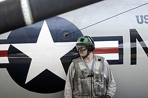 US Navy 120121-N-RG587-036 A Sailor rests against the side of a jet.jpg