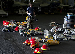 US Navy 120204-N-BT887-043 Aviation Boatswain's Mate (Handling) Airman Zachary Hickman stows firefighting equipment in the hangar bay aboard the Ni.jpg