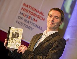 Directeur Valentijn Byvanck van het Nationaal Historisch Museum toont het boek 'Schetsen voor een Nationaal Historisch Museum'.
