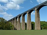 Looking up toward a metal aqueduct, supported by multiple tall, stone pillars and arches.