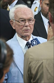 An older gentleman wearing glasses and who is bald except for a crescent of white hair at the back of his head is standing in the middle of a crowd wearing a light blue suit and dark blue tie. A man in a brown shirt whose back is turned to the camera is pointing a blue microphone with the number one at the older man.