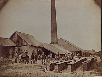 Brickworks - Men working in the yard of a brickworks in Germany, the tall chimney of the kiln visible, 1890