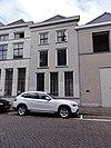 foto van Huis met schilddak en gebosseerd gepleisterde lijstgevel waarin empire schuiframen