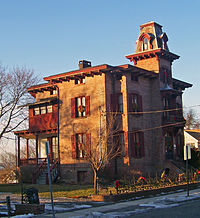 A brick house with a peaked tower and red wooden trim, seen from far to its right and illuminated by late-afternoon sun from the left