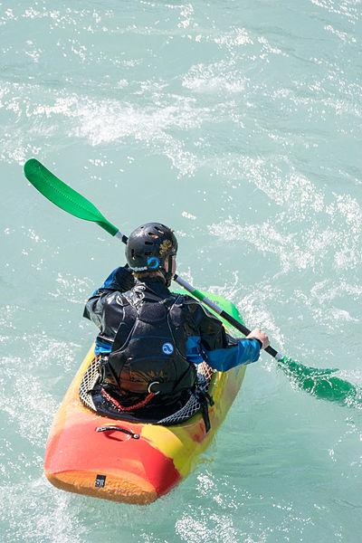 Kayaker playboating at L'Argentière-la-Bessée's canoe stadium, on the Durance river (France).
