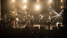 Un groupe de cinq musiciens sur une scène.