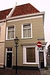 foto van Gepleisterd pand op de hoek van de Kleine Kerkstraat. Het huis telt een verdieping en een schilddak. De gevels met de geprofileerde, aan de hoeken afgeronde vensteromlijstingen hebben een 19e-eeuws karakter