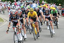 A group of cyclists, with one wearing a yellow jersey