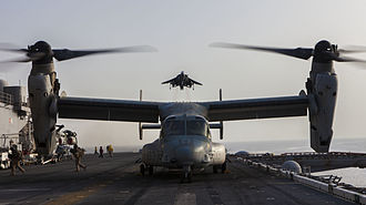 USS Kearsarge (LHD-3) - An AV-8B Harrier about to land on Kearsarge as an MV-22B Osprey prepares to launch