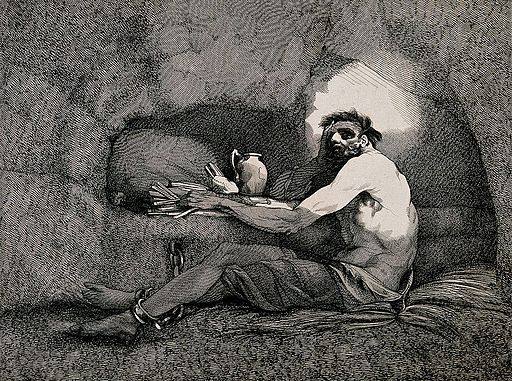 A prisoner is sitting on straw in a cave with his feet chain Wellcome V0041238
