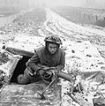 A soldier from the 1st Battalion Rifle Brigade, 7th Armoured Division, emerges from his foxhole armed with a PIAT, 28 December 1944. B13235.jpg