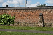 A photograph of Abbot Penny's Wall: part of the abbey precinct wall built in brick around the turn of the 16th century