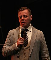 Abel Korzeniowski, standing and speaking into a hand-held microphone at a film-music festival