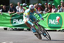 A cyclist riding a time trial while wearing a skinsuit.