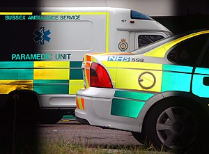 Emergency vehicle equipment - Composite picture of two ambulance vehicles in different light sources showing retroreflective high visibility battenburg markings in light and dark conditions