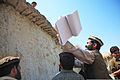 An Afghan village elder throws a notebook toward a child who waits on top of a roof during a Key Leader Engagement in Lower Nawa Village,in Konar province, Afghanistan, Sept 110906-A-RR514-861.jpg