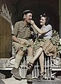 An Eighth Army soldier enjoys being fed grapes by a local girl in Sicily, August 1943. TR1247.jpg