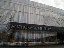 The mirrored facade of a building is seen with a stainless steel nameplate reading Anchorage Museum.
