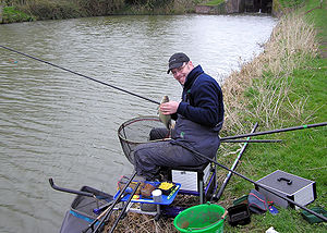 450571e1330b Man seated at the side of the water surrounded by fishing rods and tackle.