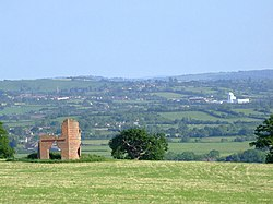 Patchwork of fields and trees with buildings showing in the distance. In the foreground is grass with a ruined building.