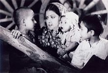 A screenshot from the film Aurat showing an Indian woman with three children.