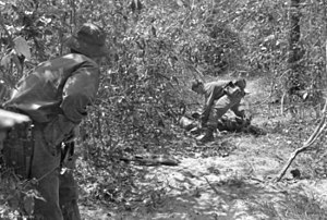 Black and white image of an Australian soldier searching the body of a dead Viet Cong while another soldier provides cover