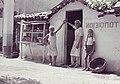 Bakker zijn knecht en een meisje bij de ingang van een bakkerij, Bestanddeelnr 254-6549.jpg