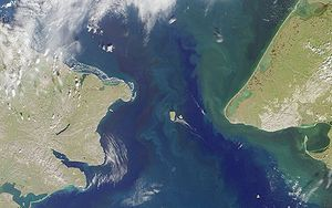 Bering Strait crossing - Satellite image of Bering Strait. Cape Dezhnev, Russia is on the left, the two Diomede Islands are in the middle, and Cape Prince of Wales, Alaska is on the right.