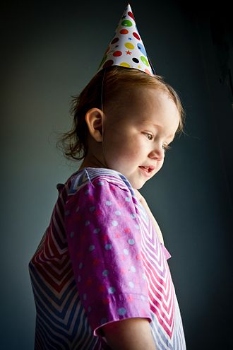 Birthday - Little girl in traditional birthday hat used in Canada and the U.S.