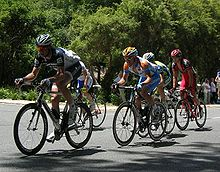A group of five cyclists on the road. Three, in the foreground, are crouched over their bicycles, while the other two are riding out of the saddle. Spectators are visible on the roadside.