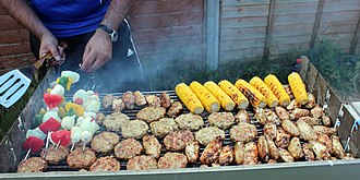 Barbecue - A British barbecue including chicken kebabs, marinated chicken wings, sweetcorn, and an assortment of vegetables.