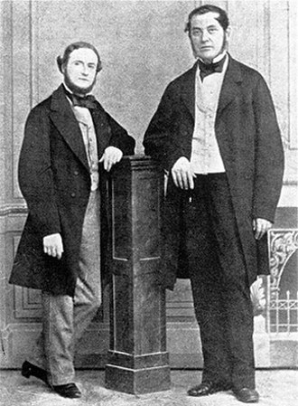 Gustav Kirchhoff -  alt= Black-and-white image of two middle-aged men, either one leaning with one elbow on a wooden column in the middle. Both wear long jackets, and the shorter man on the left has a beard.